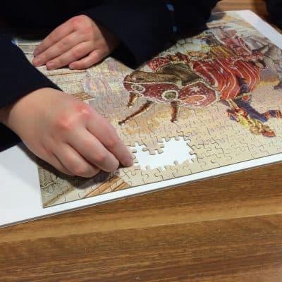 Hands assembling 1000-piece puzzle.